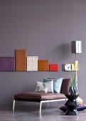 Leinwände mit Hightech-Stoffen bezogen an farbiger Wand, davor Lederliege und Keramik-Bestelltisch