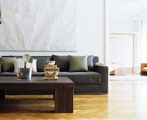 Herringbone parquet floor, coffee table and taupe couch in living room