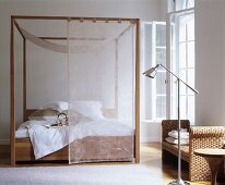 Four-poster bed with transparent curtains next to rattan bench and standard lamp