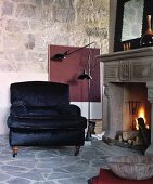 Black velvet armchair next to open fire in historical ambiance