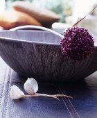 Allium flower lying across elegant bowl on leather rug