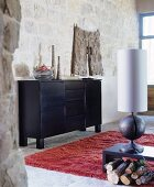 Black sideboard, table lamp with wooden base and red flokati rug in rustic living area