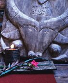 Lit candle in bowl and flower in front of ethnic carving