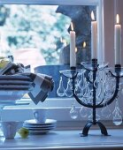 Lit candles in black candelabra with glass pendants