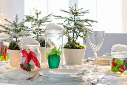 Artificial snow, small fir trees and wrapped gifts in mason jars on Christmas table