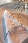 White linen napkin with drawn thread work and cow parsley seed head on plate