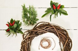 Red chillies, sage leaves, rosemary and willow wreath on white surface