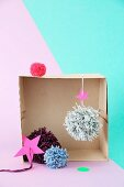 Pompoms arranged in old box in front of two-tone wall