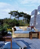 Comfortable wicker sofa and wooden tables on wooden terrace