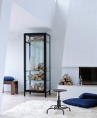 Vase and firewood in black-framed display case next to open fireplace and blue floor cushion on flokati rug