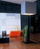 Stehleuchte mit kubischem Lampenschirm vor orangefarbenen Sitzpolstern und moderner Kunst