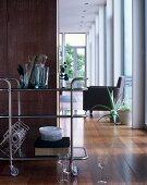 Servierwagen vor Raumteiler, Blick in Wohnbereich mit Armlehnsessel