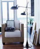 Wicker armchair with seat cushion next to black standard lamp