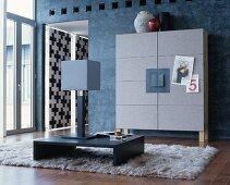 Grauer Schrank mit Filz an blaugrauer Wand, Bodentisch mit Tischleuchte auf Flokatiteppich