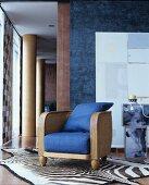 Loungesessel mit Rattangeflecht, Holz und blauen Polstern auf Zebrafellteppich