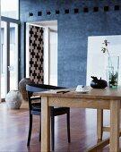 Schlichter Holztisch mit Glasvase und schwarzem Stuhl