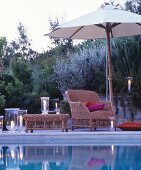 Romantic twilight ambiance: comfortable wicker armchair and lit candle lanterns next to swimming pool
