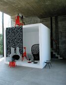 Black and red designer furniture in white cube in front of concrete wall