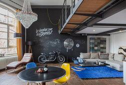 Chalkboard wall and designer furniture in open-plan loft interior