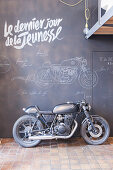Motorbike against chalkboard wall covered in chalk drawings and writing