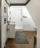 White bathroom with brown tiled floor and exposed brickwork