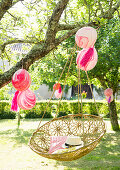 Hanging chair and marbled balloons in garden