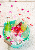 Colourful drinks in turquoise bucket filled with ice cubes and petals