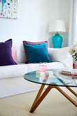 Round coffee table in front of white sofa with velvet cushions in shades of blue and purple
