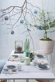 Weihnachtliche Tischdekoration mit geschmücktem Zweig