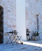 Delicate metal garden furniture against stone walls