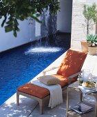 Sommerlicher Liegeplatz neben einem Pool mit Wasserfall