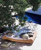 Wicker lounger below tree next to swimming pool