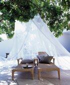Zwei Liegen mit Baldachin unter einem Baum auf mediterraner Terrasse