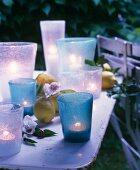 Teelichter in Glasgefässen zwischen Blüten und Zitronen als sommerliche Tischdeko