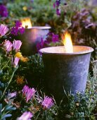 Lit candles in flowerbed at twilight