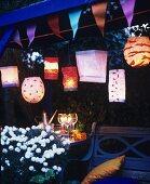 Wimpelkette und verschiedene Papierlampions als stimmungsvolle Gartendekoration