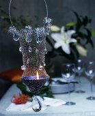 Ornate, suspended, wire-mesh candle holder decorated with crystals