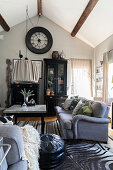 Grey sofa and zebra-skin rug in living room with display cabinet under wall-mounted clock
