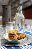 Silver dish of biscuits and swing-top bottle on garden table