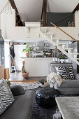 Grey sofa set, staircase and kitchen in open-plan interior
