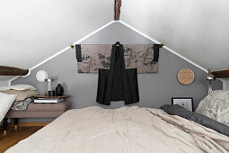 Double bed in attic room with Japanese Haori hung on grey wall