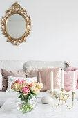 Rosenstrauß in Kugelvase und Kerzenhalter auf Couchtisch, im Hintergrund Goldrahmen-Spiegel über Sofa mit Dekokissen