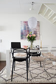 White table and black and transparent chairs on pale rug in dining area