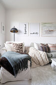 Various blankets and cushions on récamier and sofa under pictures on wall