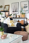 Armchair and pouffe in front of ornaments on open shelves