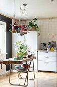Alte Werkbank mit Pflanzen in der Küche mit Möbelmix