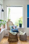 Bunte Kissen auf einem Korbsessel vor dem Fenster mit Zimmerpflanzen