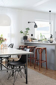 Dining table next to grey kitchen counter with bar stools