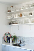 Crockery and groceries on open kitchen shelves above sink