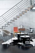 Designer chairs, floating staircase and concrete wall